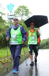 雨の中、奄美大島を元気に歩く(左から)花牟礼さんと塩川さん=29日、龍郷町