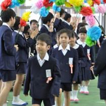 在校生らに見守られ、入場する新1年生=8日、奄美市の名瀬小学校