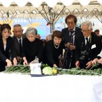 祭壇に献花して犠牲者のみ霊を慰める遺族ら=17日、徳之島町亀徳
