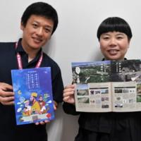 製作した世之主ガイドブックをPRする、かなめデザインの要笑子さん(右)と企画課の森さん=15日、和泊町役場