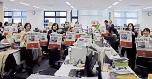 新元号「令和」を報じる南海日日新聞の号外を手にする奄美市役所職員=1日、奄美市名瀬