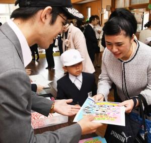 新1年生と保護者に防犯啓発グッズなどを手渡す奄美署員(左)=8日、小宿小学校