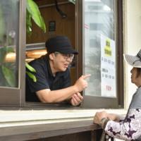 店の窓から住民へ声を掛ける店主の原田さん=12日、奄美市名瀬