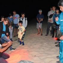 ウミガメ観察時の注意点を説明する興会長(左)=6日、奄美市名瀬の大浜海岸