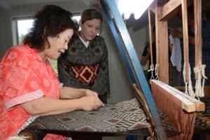 大島紬の織り方の説明を受ける英字フリーペーパー記者のリサさん(左から2人目)=20日、龍郷町