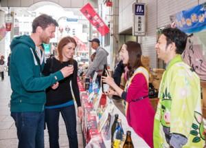 外国人観光客にも味と香りが好評だった奄美黒糖焼祭り=9日、大阪・天神橋二丁目商店街