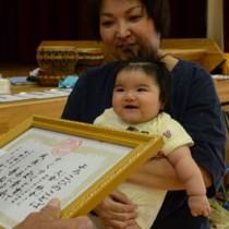 「よろこびの言葉」に満面の笑みをみせる久倉紗音ちゃん(中央)と母親の千登勢さん(右)=5日、宇検村田検