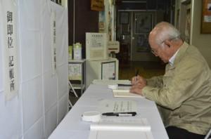 退位と即位に合わせて設置された記帳所で、新時代への思いを込め記帳する市民=1日、奄美市名瀬の県大島支庁