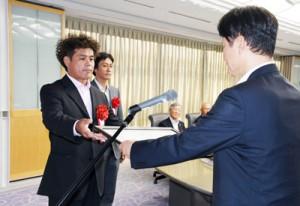 表彰状を受け取る中村理事長(左)=23日、鹿児島市の県庁