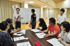 グループごとに演習を行う研修参加者=18日、和泊町