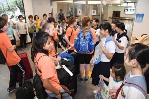 米国から派遣された交流生らを歓迎する奄美市の生徒ら=29日、奄美市笠利町の奄美空港