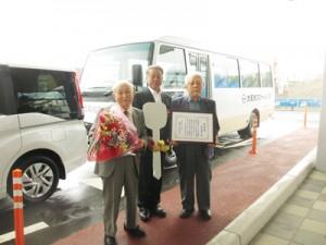 マイクロバスと福祉車両を大和村に寄贈した才納さん(右)(大和村提供)