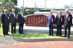 美智子さまが詠まれた歌を記した御歌碑と、除幕式の出席者ら=12日、知名町