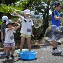ジャンボシャボン玉に夢中の子どもたち=5日、奄美市名瀬の県立奄美少年自然の家