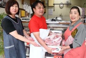 豚肉を贈呈する㈲宮本商店の宮本代表(中央)とNPOの西野代表=徳之島町亀津