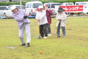 直前までの雨でコンディションが悪い中でも、プレーを楽しむグラウンド・ゴルフ参加者=29日、和泊町