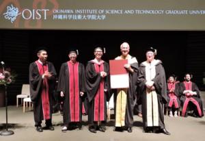 ピーター・グルース学長(右から2人目)から学位記を授与された濱田太陽さん(中央)=25日、沖縄県恩納村
