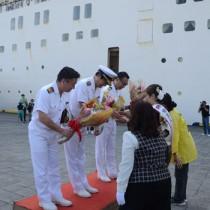 紬美人らから歓迎の花束を受け取るぱしふぃっくびいなす関係者=4日、奄美市の名瀬観光船バース