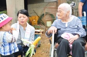 収穫したトウモロコシを話題にしながら交流するひだまりの入所者と子どもら=2日、和泊町