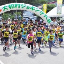 一斉にスタートを切る2㌔コースの参加者=26日、大和村の村体育館前