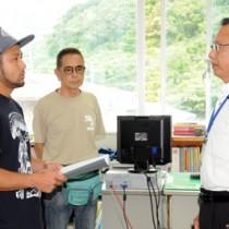 クルーズ船寄港地開発計画の白紙撤回を求める要望書を提出する加計呂麻島の住民(左)=9日、瀬戸内町役場