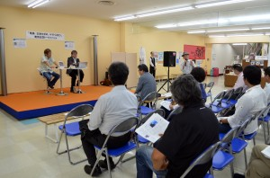 トークイベントで本の内容を紹介する(ステージ上、左から)斎藤さんと前利さん=4月25日、沖縄県那覇市