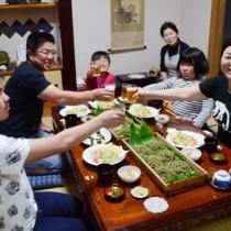 農家民宿「ほおらしゃ家」で夕飯を楽しむ熊本県の荒井弘幸さん一家=3日、奄美市住用町