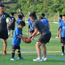 元日本代表の吉田さん(左)からラグビーを教わる教室参加者=11日、与論町