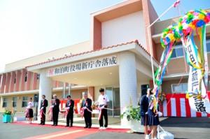 テープカットし、くす玉を割って新庁舎の落成を祝った記念式典=19日、和泊町役場