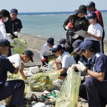 集めたごみの種類や国籍を調査する生徒ら=23日、龍郷町嘉渡海岸