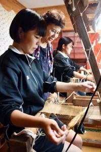 武島さん(中央)に芭蕉布の技術を学ぶ生徒ら=20日、伊仙町