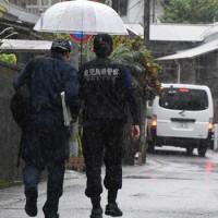 事件があった現場の民家へ向かう捜査関係者=19日午前8時50分ごろ、奄美市名瀬小俣町