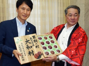 特産のスモモを三反園知事に手渡す伊集院村長(右)=7日、鹿児島市の県庁