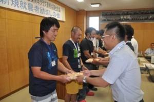 先輩農家から記念品を受け取る新規就農者(左側)=27日、知名町