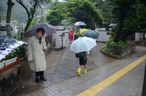 地域住民らに見守られながら登校する奄美小学校の児童=同日午前7時半すぎ、奄美市名瀬