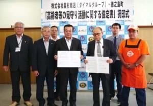 高齢者の見守り活動に関する協定書を交わした徳之島町と㈱義村商店の関係者ら(提供写真)