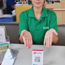 店頭にあるQRコードをスマホのアプリで読み取る仕組みのキャッシュレス決済=12日、ヨロン島観光協会事務所