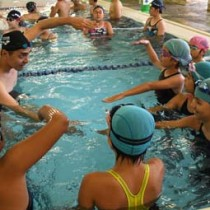子どもたちへ水中での手の使い方を指導する伊藤さん(左)=26日、伊仙町伊仙