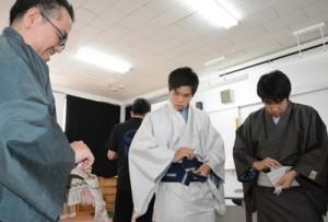 講師の手本を見ながら帯を締める生徒=12日、奄美市笠利町