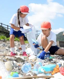 海岸のごみを拾う円小の児童=12日、龍郷町