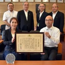 朝山市長(後列中央左)に「はばたく商店街30選」入りを報告した惠会長(前列左)=10日、奄美市役所