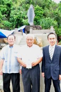 東委員長(中央)に目録を手渡した吉田署長(右)。後ろは現在、整備改修中の慰霊碑=4日、知名町知名