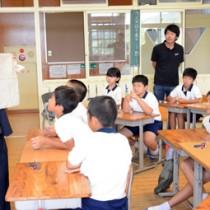 柳と泥で染めた布を大勝小児童に紹介する泉二啓太さん(左)=18日、龍郷町