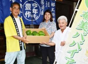 ホテルに島内産パパイアを贈った熊元部会長(左)=20日、徳之島町亀津
