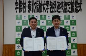 協定書を手に笑顔を見せる(左から)元山公知宇検村長と東北福祉大の草間吉夫特任教授=11日、宇検村