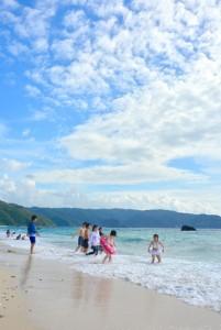 梅雨明けの青空の下、海水浴客でにぎわった浜辺=13日、奄美市名瀬の大浜海浜公園