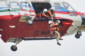 地上40㍍の高さでホバリングする防災ヘリに救助される病傷人=7日、龍郷町
