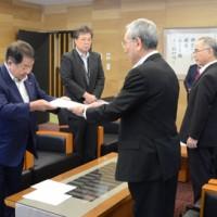 朝山理事長に報告書を手渡す谷会長(左)=18日、奄美市役所