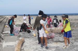 海岸に打ち上げられたごみを拾い集める参加者たち=14日、小野津