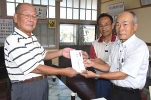 町内の小中学校に商品券を贈呈した伊仙町商工スタンプ会の佐藤会長(右)=17日、同町伊仙